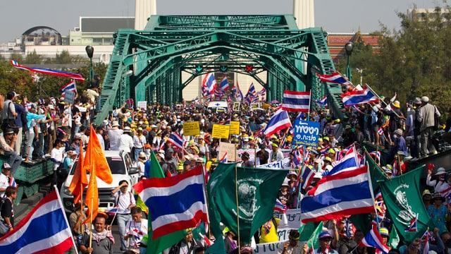 Menschen mit thailändischer Flagge auf einer Brücke.
