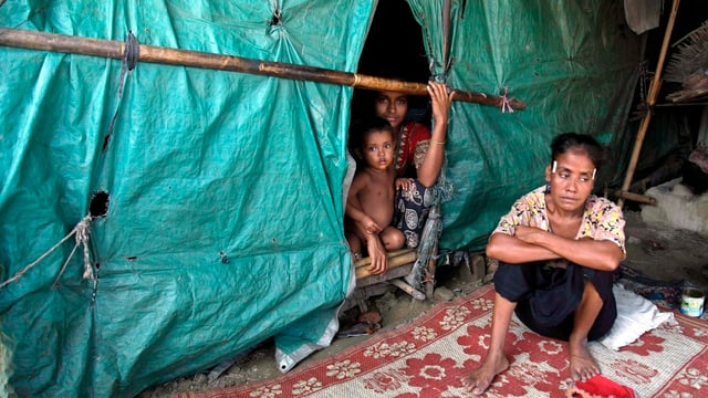 Zwei Flüchtlingskinder in einer Hütte aus Planer, davor sitzt eine Frau.