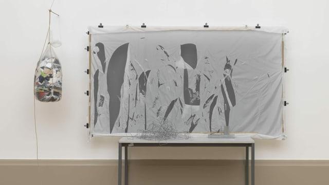Ein Gemälde auf einem Tisch, daneben hängt ein Sack von der Wand.