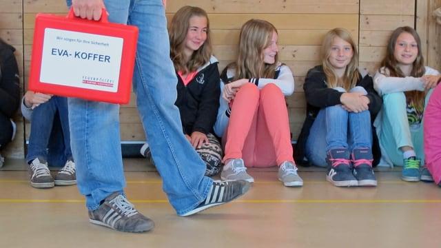 Schülerinnen sitzen in einer Turnhalle, an ihnen läuft ein Mann mit einem roten Koffer vorbei.