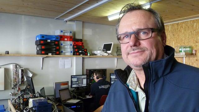 Der Chef der Zeitmessung, Eckhard Frank, vor dem Pult mit den Computern und einem Mitarbeiter.