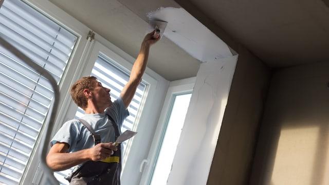 Ein Mann streicht eine Wand.