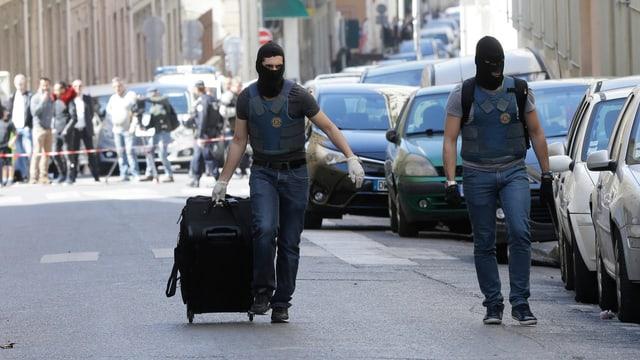 Dus policists portan davent ina valischa gronda suenter la tschertga en la casa a Marseille.