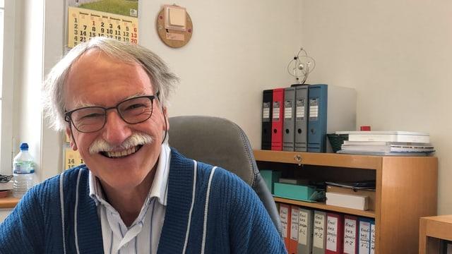 Ein Mann mit grauen Haaren und buschigem Schnauz lächelt in einem Büro in die Kamera.
