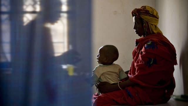 Eine Mutter mit ihrem kleinen Kind beim Arzt.