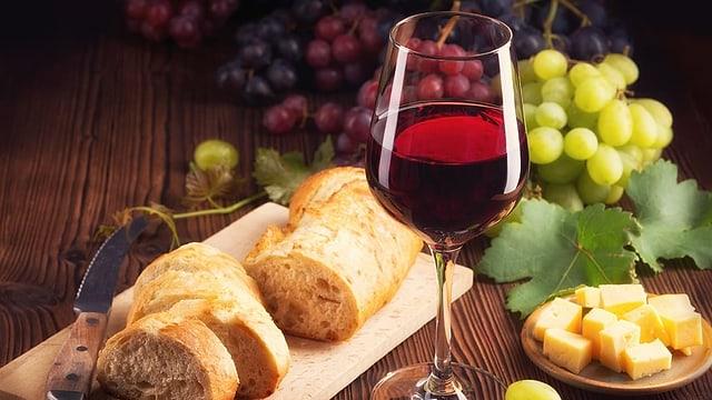 Blick auf Käse, Trauben, Brot und ein Glas Wein