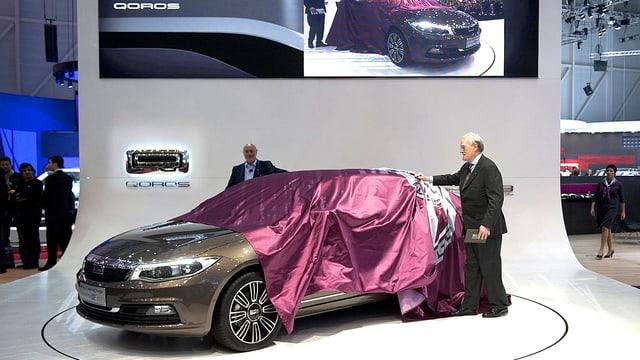 Zwei Präsentatoren ziehen die violette Sichtschutz-Plane von einem neuen Modell des Qoros anlässlich seiner erstmaligen Präsentation am Genfer Automobilsalon im Frühjahr 2013.