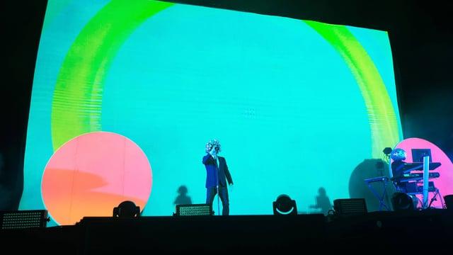 Die Pet Shop Boys auf einer schrillen Bühne: der Hintergrund leuchtet türkis, rosa und grün.