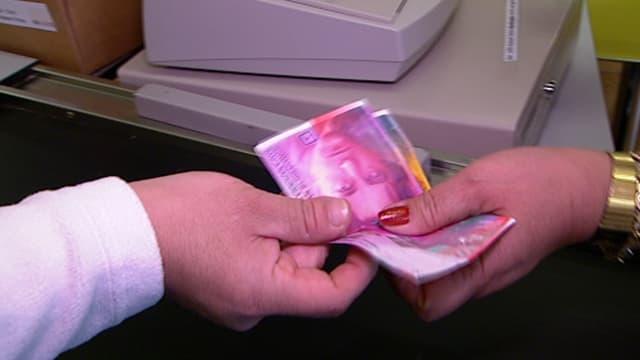 Eine Person übergibt einer Frau an der Kasse 30 Franken.