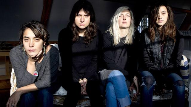 Vier Frauen der Band Warpaint sitzen und schauen ins Bild.
