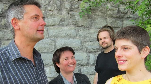 Eine Gruppe von vier Personen vor einer Mauer.