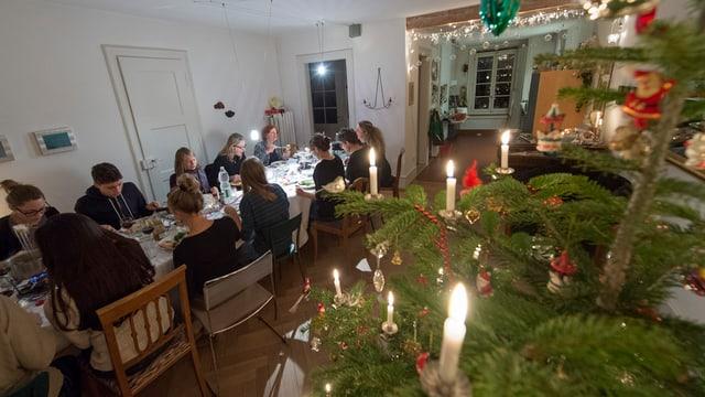 Viele Menschen sitzen an einem Tisch und essen. Rechts im Bild-Vordergrund sieht man Teile eines Weihnachtbaums.