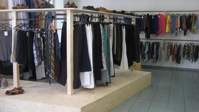 Schlichte Kleiderstangen auf Spanplattenkonstruktionen, das schlichte Innere des Caritasladen.
