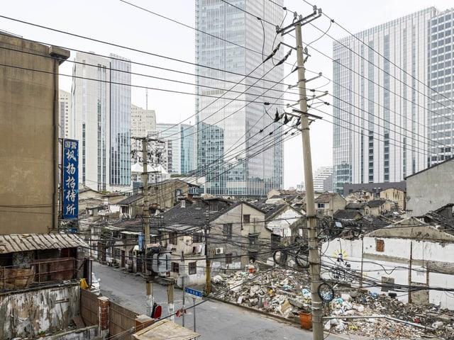 Zerfallende Häuser im Vordergrund, Hochhäuser im Hintergrund.