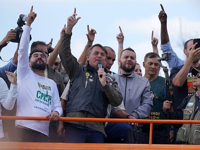 Bolsonaro (ohne Maske) spricht vor Anhängern (ebenfalls ohne Maske)