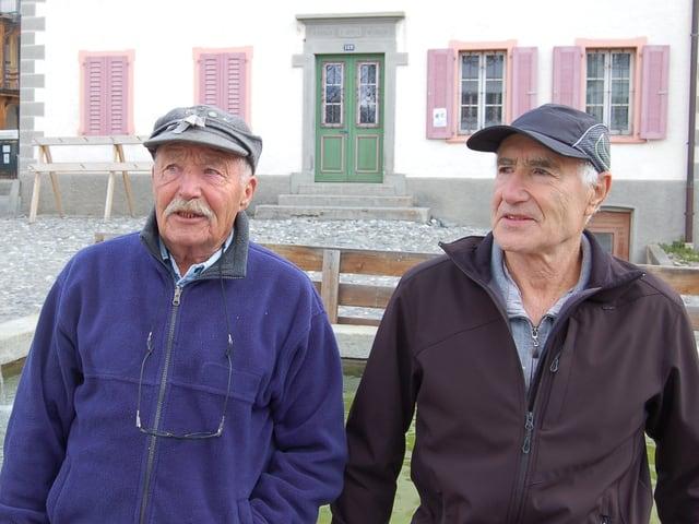 Zwei Männer sitzen auf einem Brunnenrand.