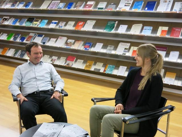 Karl Böhlen und Sara Schumacher sitzen vor einem Gestell mit theologischen Schriften.