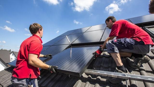Handwerker montieren bei strahlendem Wetter Solarpaneele auf einem Schrägdach.