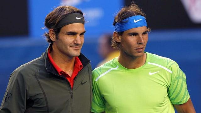 Zu sehen sind die beiden Tennisspieler Roger Federer und Rafael Nadal vor einem Tennisspiel. Sie stehen nebeneinander und sind noch nicht verschwitzt.