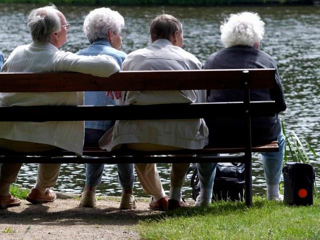 Fünf Senioren sitzen auf einer Bank an einem Gewässer.