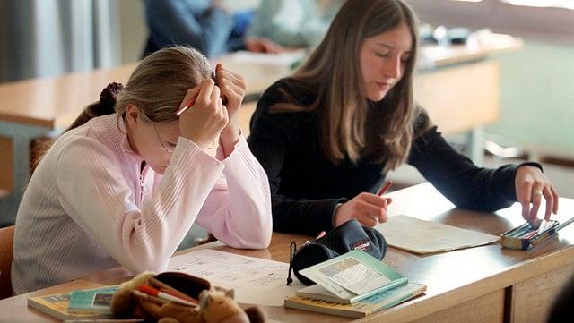 Zwei Mädchen am Schulbank.