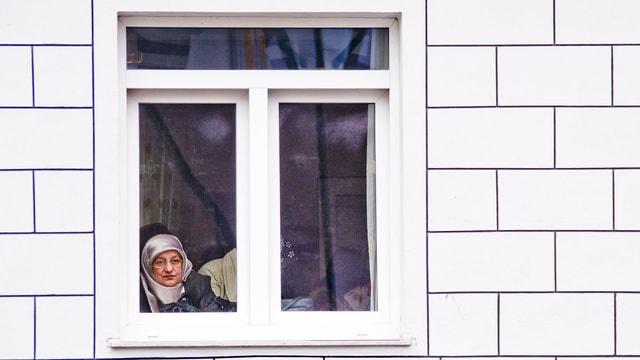Eine Frau mit Schleier schaut aus einem Fenster.