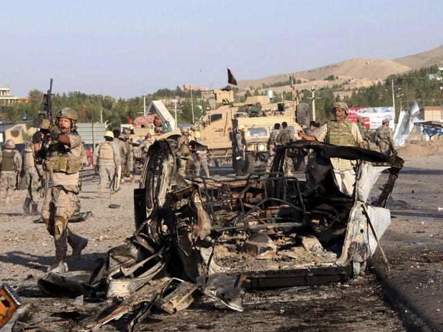 Schwer bewaffnete Soldaten vor einem zerstörten Fahrzeug.