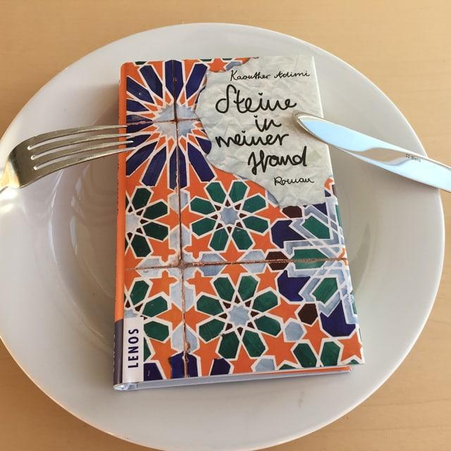 Der Roman «Steine in meiner Hand» von Kaouther Adimi liegt auf einem weissen Teller, Messer und Gabel darüber.