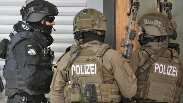 Trais polizist cun armas.