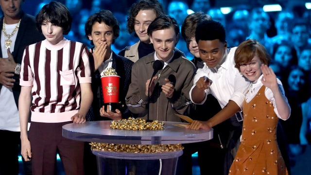 Mehrere Jugendliche, die um einen Glastisch mit einer Trophäe stehen.