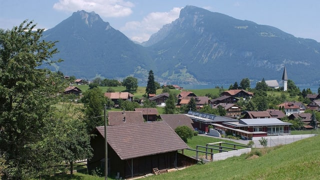 Blick auf das Dorf Faulensee, Berge im Hintergrund.
