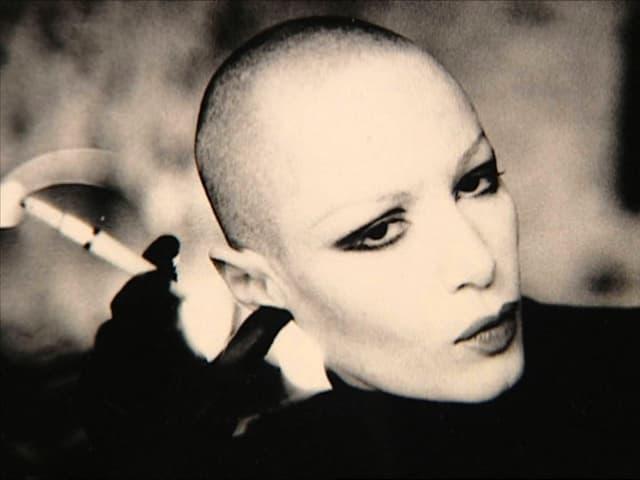 Manon, mit kahlrasiertem Kopf und Zigarette.