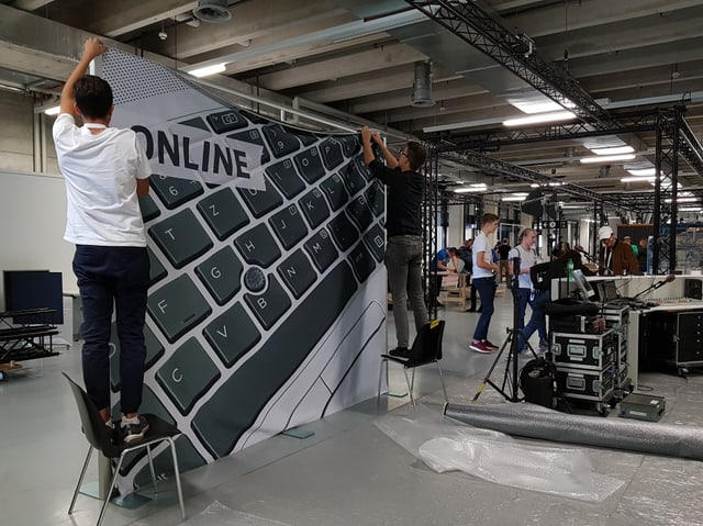 Zwei Lernende bauen am Stand der SRG an den Swissskills 2018.
