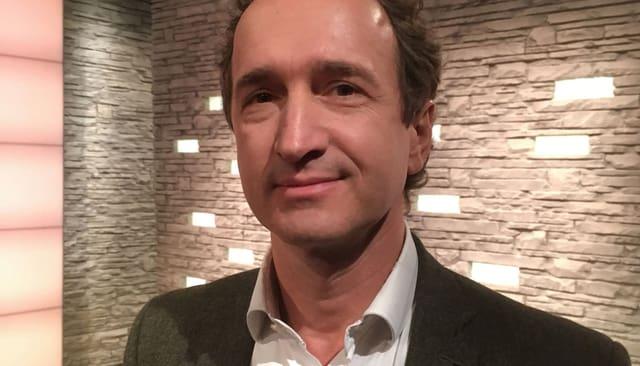Ein Mann lächelnd in einem TV-Studio.