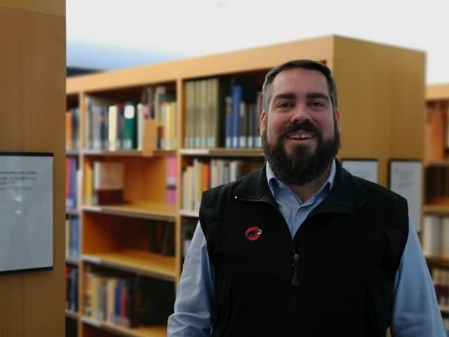 Mann mit Bart vor Bücherregal.