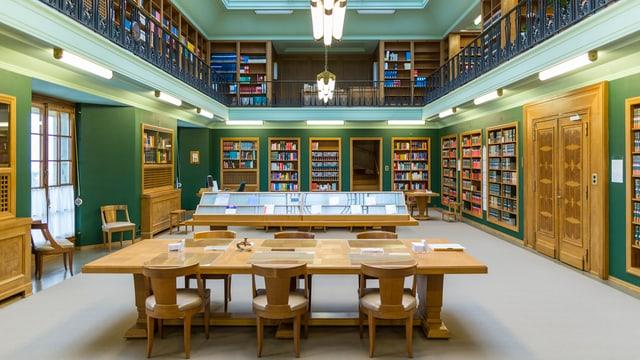 Ina biblioteca cun maisas e cudeschs.