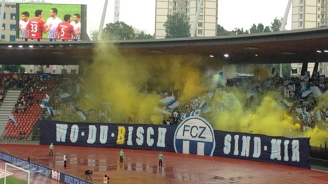 """Transparent mit der Aufschrift """"Wo du bisch - FCZ - sind mir"""", die Südkurve vernebelt mit gelbem Pyrorauch."""