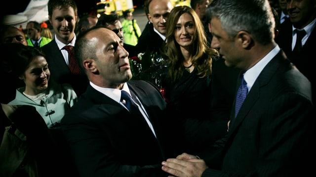 Zwei Männer schütteln sich die Hand, umringt von weiteren Menschen.