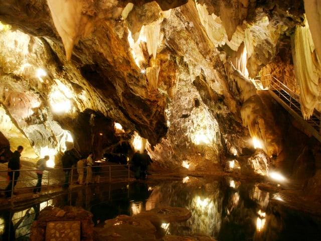 Beleuchtete, grosse Höhle, von welcher Tropfsteine herunterhängen.