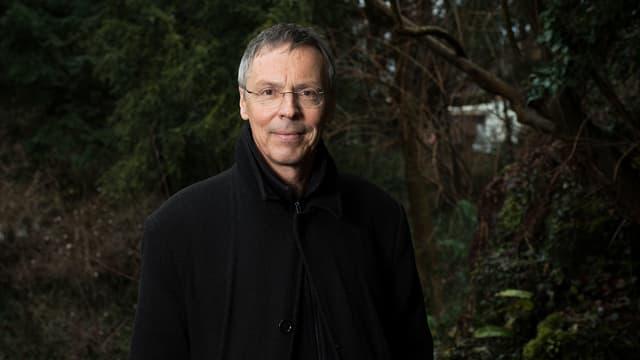 Raimund Rodewald steht vor Nadelbäumen.