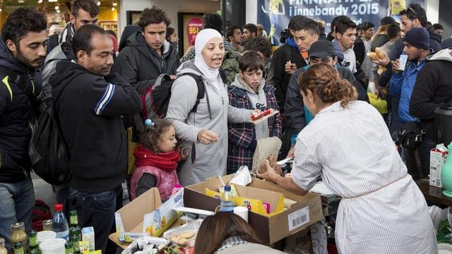 Zwei schwedische Frauen im Gespräch mit Frauen und Männern, an einem improvisierten Stand, auf dem Lebensmittel stehen.