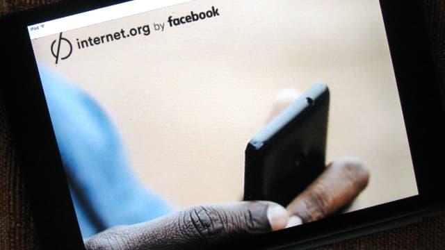 Eine Bildschirmaufnahme von «Free Basics». Man sieht eine Hand mit einem Smartphone.