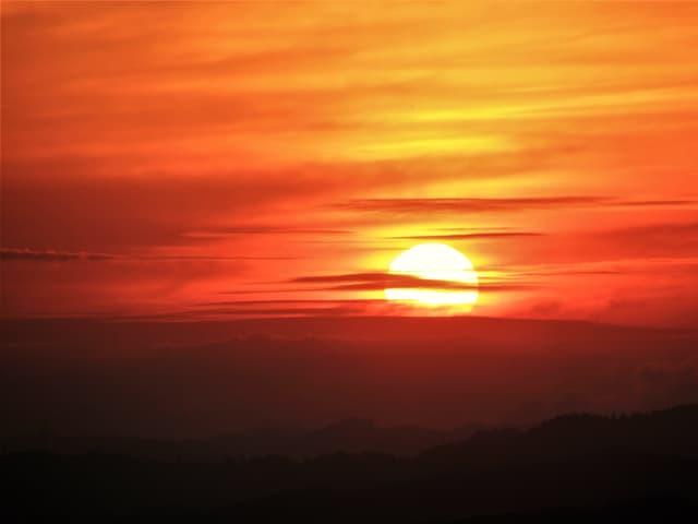 Die aufgehende Sonne an einem roten Himmel.