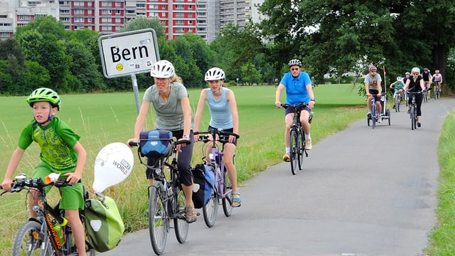 Velofahrerinnen und Velofahrer unterwegs in Bern-Wittigkofen.