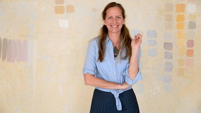 Eine Frau in hellblauem Hemd steht vor einer mit dezenten Farben bemalter, beiger Wand.