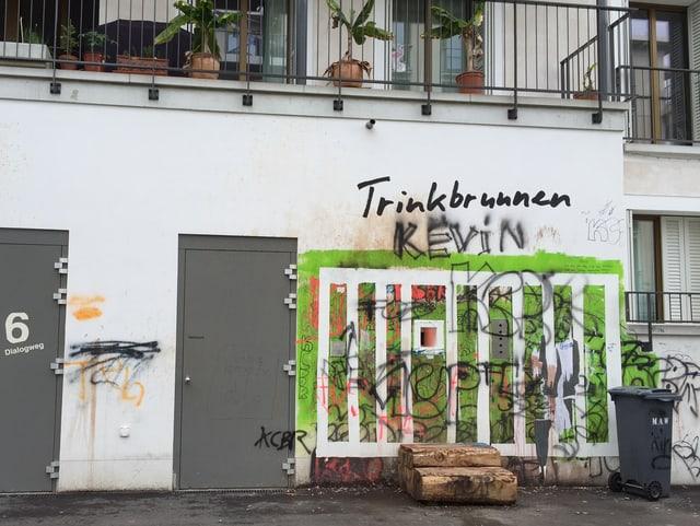 Der Getränke-Automat von Weitem. Obendran das Geländer eines Balkons. Rechts davon eine Mülltonne.