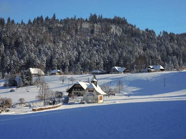 Verschneite Landschaft mit ein paar Häusern.