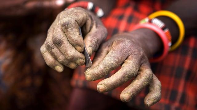 Ein paar Hände, die rechte hält eine Art Metallspachtel.
