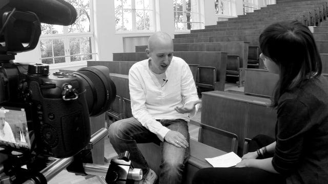 Schwarz-weiss Bild mit Reporterin, Interviewpartner und Kamera im Bild.