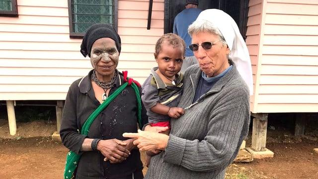 Eine Ordensschwester hält ein Kind auf dem Arm. Neben ihr steht eine andere Frau.